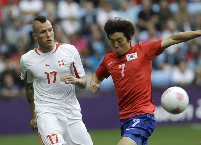 South Korea's Kim Bok-yung, right, battles for the ball against Switzerland's Michel Morganella during their group B men's soccer match between South Korea and Switzerland at the London 2012 Summer Olympics, in Coventry, England, Sunday, July 29, 2012. (AP Photo/Hussein Malla)