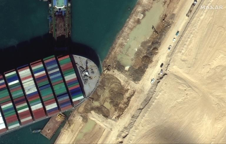 This satellite imagery released by Maxar Technologies shows tug boats and dredgers on March 27, 2021, attempting to free the Taiwan-operated MV Ever Given lodged sideways and impeding all traffic across Egypt's Suez Canal