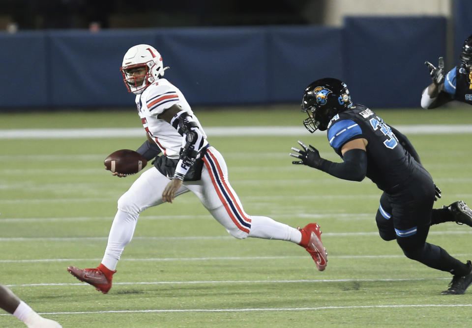 Liberty quarterback Malik Willis (7) runs upfield past Coastal Carolina linebacker Teddy Gallagher (34) during the first half of the Cure Bowl NCAA college football game Saturday, Dec. 26, 2020, in Orlando, Fla. (AP Photo/Matt Stamey)