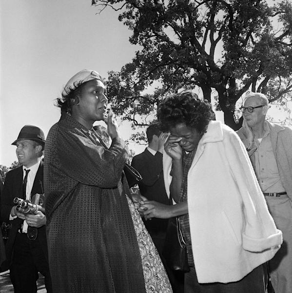 FILE - In this Nov. 22, 1963 file photo, women burst into tears outside Parkland Hospital upon hearing that President John F. Kennedy died from a shooting while riding in a motorcade in Dallas. Looking at why so many black people revered him then - and why younger generations have largely forgotten his civil rights work now - shows that even 50 years later, Kennedy holds a complicated but pivotal place in black history. (AP Photo/File)