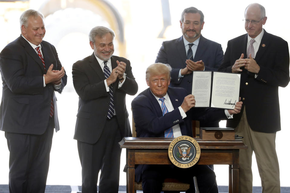 President Donald Trump holds up a permit for energy development after signing it during a visit to the Double Eagle Energy Oil Rig, Wednesday, July 29, 2020, in Midland, Texas. Sen. Ted Cruz, R-Texas, stands rear, second from right. (AP Photo/Tony Gutierrez)