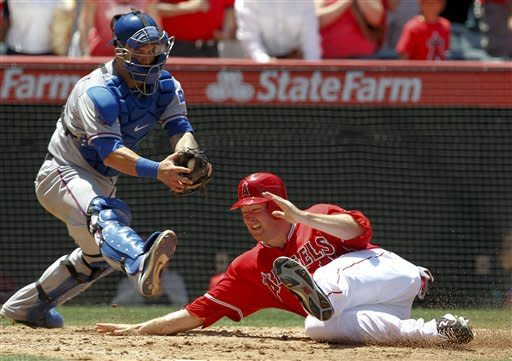 Los Angeles Angels' Mark Trumbo, right, scores under the tag of Texas Rangers catcher Mike Napoli on a Erick Aybar double during the fifth inning of a baseball game in Anaheim, Calif., Sunday, June 3, 2012. (AP Photo/Chris Carlson)