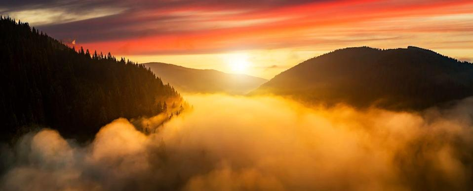 <p>Sunrise over mist-covered mountains in Austria. </p>