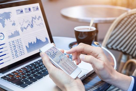Person holding phone with stock charts on it, sitting in front of a computer.