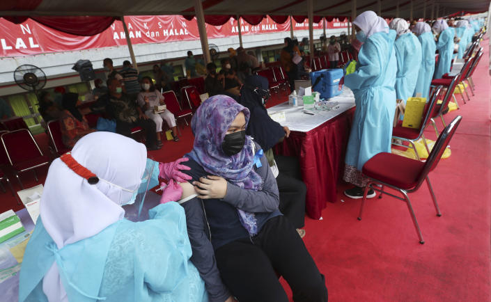 A woman receives a shot of the Sinovac vaccine for COVID-19 during a vaccination campaign at the Patriot Candrabhaga Stadium in Bekasi on the outskirts of Jakarta, Indonesia, Thursday, July 1, 2021.(AP Photo/Achmad Ibrahim)