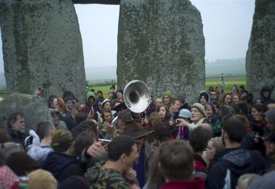 Revelers celebrate during the summer solstice at the ancient Stonehenge monument on Salisbury plain in southern England June 21, 2012.