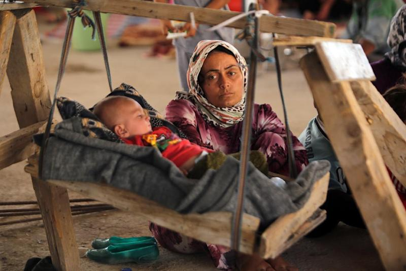 An Iraqi Yazidi woman, who fled her home when Islamic State (IS) militants attacked the town of Sinjar, looks at her baby as they rest inside a building under construction outside the Kurdish city of Dohuk, on August 16, 2014 (AFP Photo/Ahmad al-Rubaye)