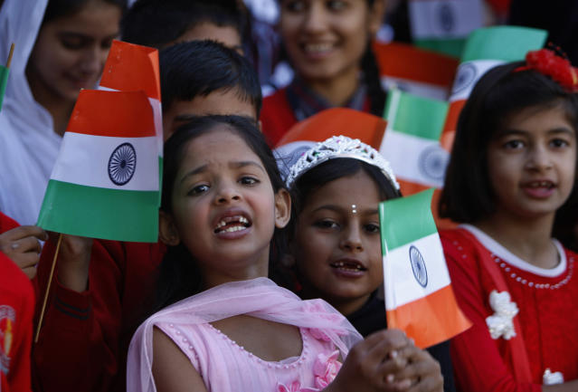 Indian school children wave Indian flags as they gather to honor Indian cricketer Sachin Tendulkar in Jammu, India, Thursday, Nov. 14, 2013. Tendulkar plays his world-record 200th and last test from Thursday in a hometown stadium for which tickets could have been sold 10 times over and still not satisfied demand. (AP Photo/Channi Anand)