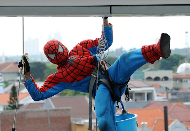 SURABAYA, INDONESIA - JULY 12: Indonesian 'Spider-Man' window cleaner, 37-year-old Teguh looses his balance before continuing to clean the glass windows of the 18-storey Alana Hotel on July 12, 2013 in Surabaya, Indonesia. Teguh is a specialist glass window cleaner working on high-rise buildings wearing a Spider-Man uniform and working at an altitude of over 500 meters above ground level. He earns between Rp. 5 million and 15 million depending on the height of the building and the level of difficulty. (Photo by Robertus Pudyanto/Getty Images)