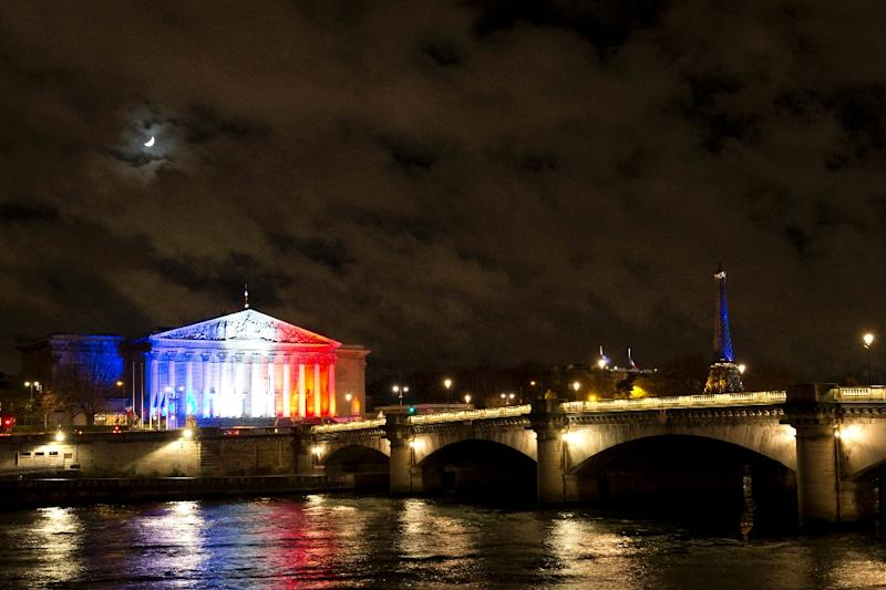 A photo taken on November 17, 2015 in Paris shows the moon shining over the French National Assembly (L) illuminated with the national colors in tribute to the victims (AFP Photo/Joel Saget)