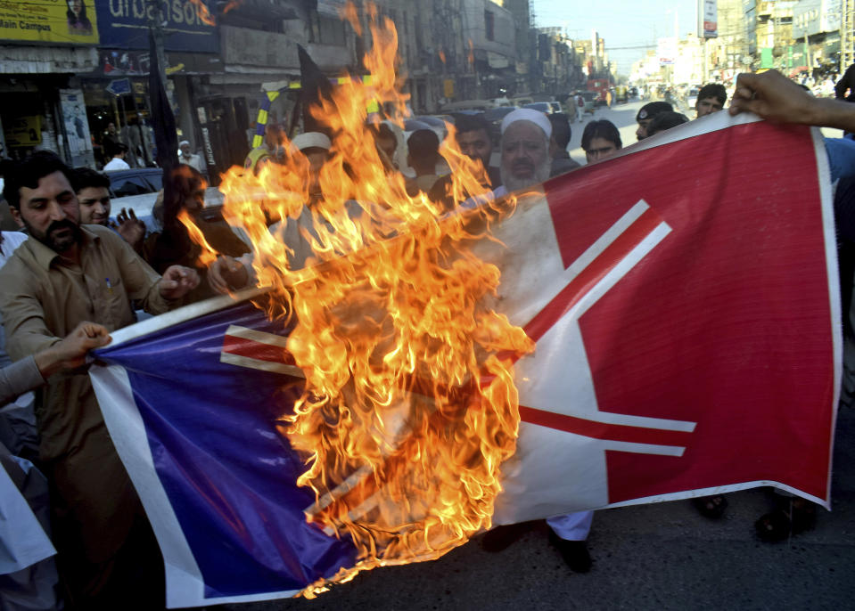 Pakistan traders burn burn a representation of the French flag during a protest against the publishing of caricatures of the Prophet Muhammad they deem blasphemous, in Peshawar, Pakistan, Monday, Oct. 26, 2020. Pakistan's Prime Minister Imran Khan said the French leader chose to encourage anti-Muslim sentiment and deliberately provoke Muslims by encouraging the display of blasphemous cartoons targeting Islam. (AP Photo/Muhammad Sajjad)
