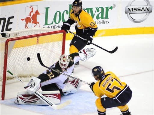Nashville Predators forward Gabriel Bourque (57) scores past Minnesota Wild defenseman Mike Lundin (2) as the Predators center Nick Spaling (13) looks on during the second period of an NHL hockey game on Tuesday, April 3, 2012, in Nashville, Tenn. (AP Photo/Mike Strasinger)