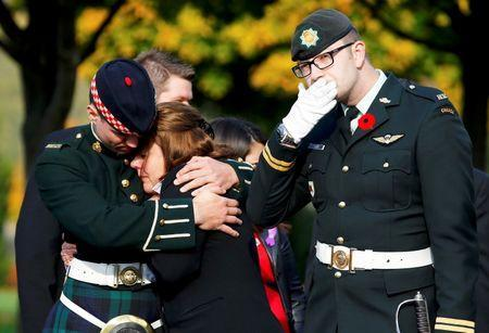 Kathy Cirillo is comforted during the funeral procession for her son, Cpl. Nathan Cirillo in Hamilton, Ontario October 28, 2014. REUTERS/Mark Blinch