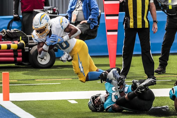 Chargers running back Austin Ekeler (30) slips the tackle of Panthers linebacker Jeremy Chinn for a first half touchdown.