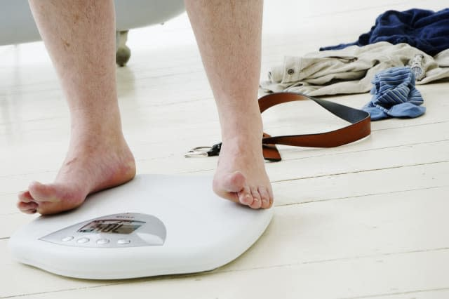 Man standing on scales by clothes and belt, low section, close-up