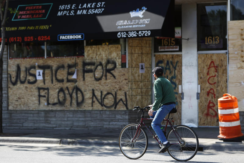 A man rides past Fiesta Mexicana Y Mas along Lake Street, Saturday, May 30, 2020, in Minneapolis. Outrage following the death of George Floyd, who died after being restrained by Minneapolis police officers on May 25, has led to the burning of businesses along the the Lake Street corridor where immigrants have found success. (AP Photo/Julio Cortez)