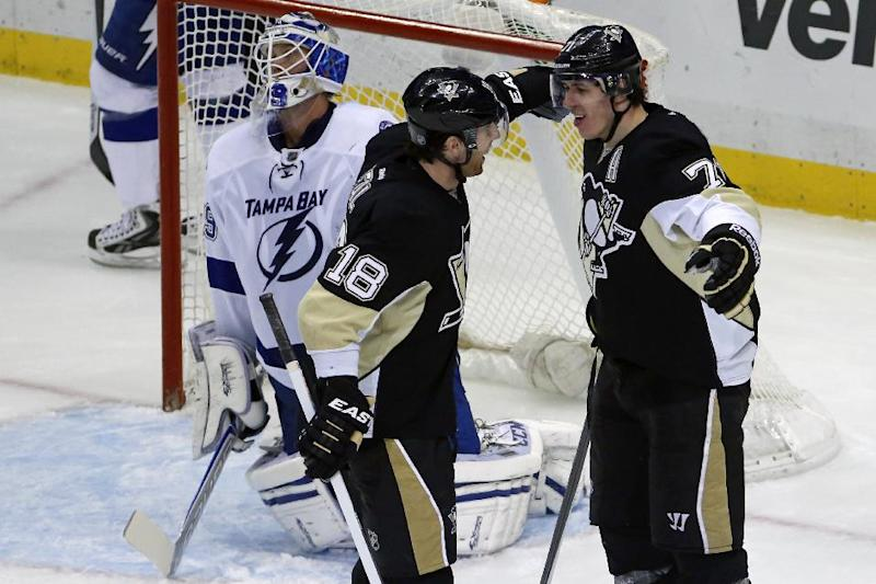 Pittsburgh Penguins' Evgeni Malkin (71) celebrates with James Neal (18) after lifting a backhand shot over Tampa Bay Lightning goalie Anders Lindback, left, for a goal in the third period of an NHL hockey game in Pittsburgh, Saturday, March 22, 2014. Malkin had two goals and two assists in the Penguins 4-3 overtime win. (AP Photo/Gene J. Puskar)