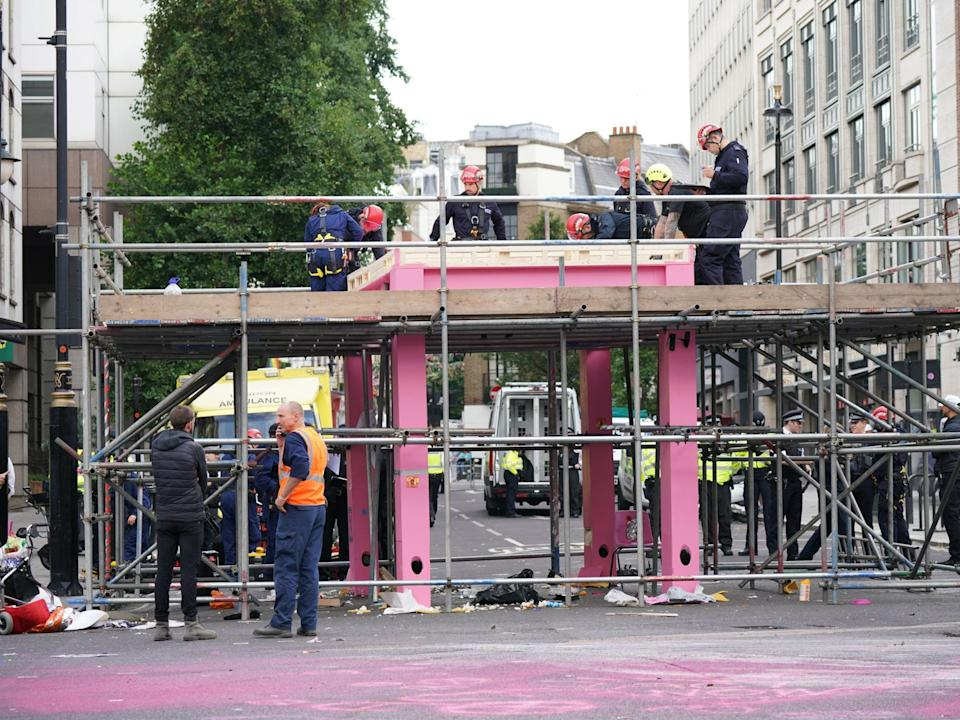 Workers remove the table, which was blocking the junction of Long Acre and Upper St Martin's Lane, on Tuesday morning (PA)