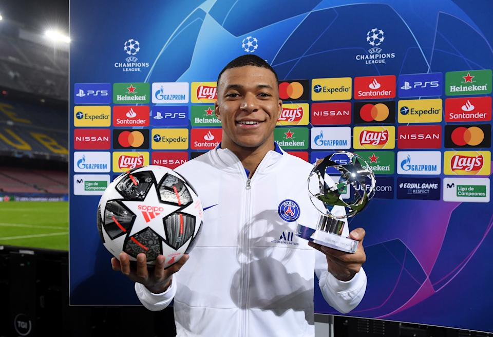 BARCELONA, SPAIN - FEBRUARY 16: Kylian Mbappe of Paris Saint-Germain poses for a photo with the match ball and the player of the match award after the UEFA Champions League Round of 16 match between FC Barcelona and Paris Saint-Germain at Camp Nou on February 16, 2021 in Barcelona, Spain. Sporting stadiums around Spain remain under strict restrictions due to the Coronavirus Pandemic as Government social distancing laws prohibit fans inside venues resulting in games being played behind closed doors. (Photo by Alex Caparros - UEFA/UEFA via Getty Images)
