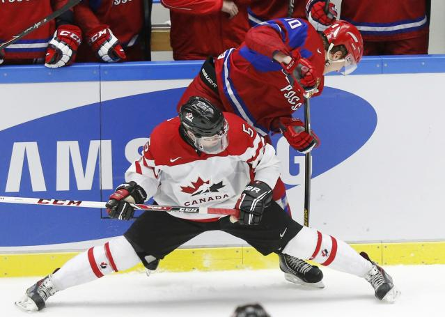Russia's Bogdan Yakimov (R) battles for the puck with Canada's Aaron Ekblad during the third period of their IIHF World Junior Championship bronze medal ice hockey game in Malmo, Sweden, January 5, 2014. REUTERS/Alexander Demianchuk (SWEDEN - Tags: SPORT ICE HOCKEY)
