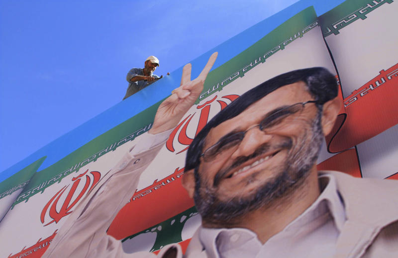 A worker fixes a huge poster of Iranian President Mahmoud Ahmadinejad during preparations for his visit in the southern village of Bint Jbeil, Lebanon, Tuesday, Oct. 12, 2010. During Ahmadinejad's Oct. 13-14 visit, he plans to stop at sites including Bint Jbeil, a border village that was bombed during the 2006 Israeli-Hezbollah war. It is barely two and a half miles (four kilometers) from the Israeli border. (AP Photo/Mohammed Zaatari)