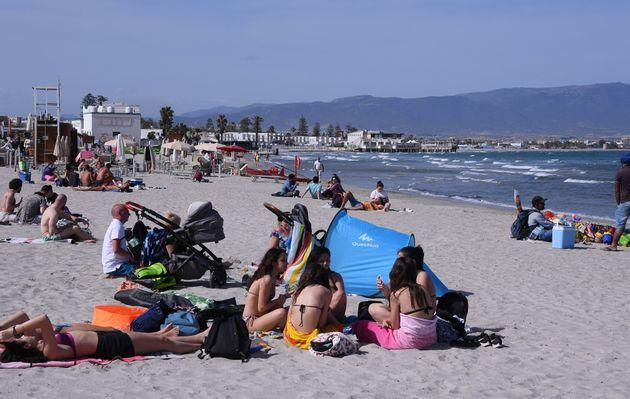 People relax on a beach in Cagliari, Sardinia, Italy, on May 28, 2021. All Italian regions have turned to