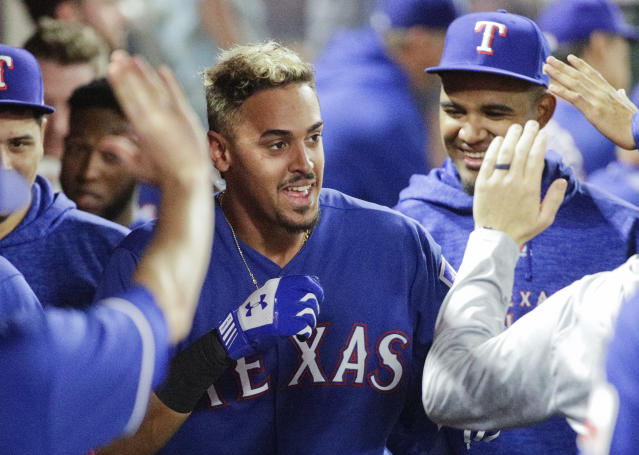 Texas Rangers' Ronald Guzman, center, celebrates in the dugout after a home run against the Los Angeles Angels during the second inning of a baseball game in Anaheim, Calif., Monday, Sept. 24, 2018. (AP Photo/Chris Carlson)