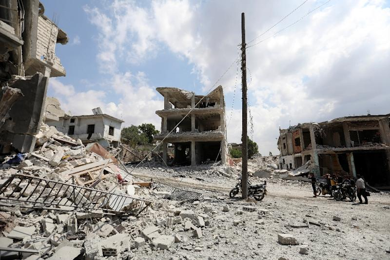 A picture taken on June 14, 2019, shows people gathering next to a damaged building in the town of Ihsim, in Syria's Idlib region, scene of heavy bombardments by Syrian government forces and its ally Russia