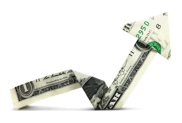 A dollar bill folded into the shape of an arrow and pointed up.