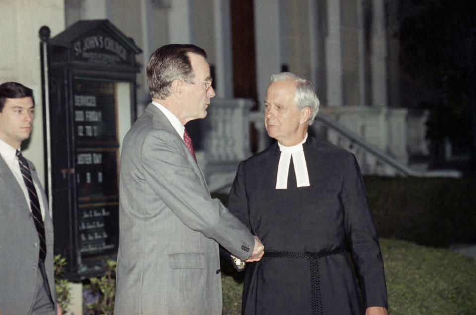 FILE - In this April 13, 1990 file photo, President George Bush is escorted by Rector John Harper, of St. John's Episcopal Church, following early morning Good Friday services in Washington. (AP Photo/Marcy Nighswander)