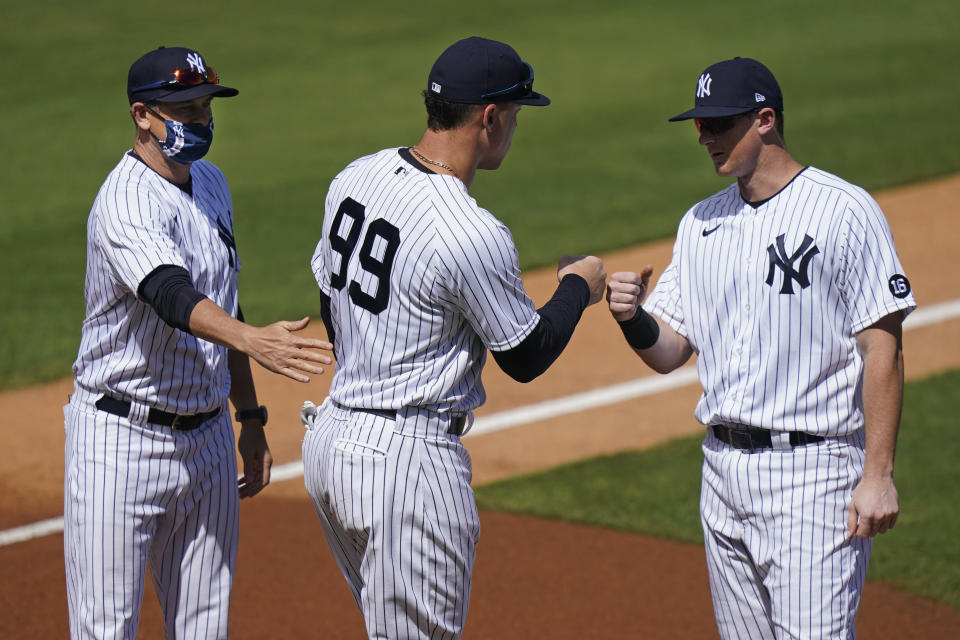 New York Yankees' Manager Aaron Boone, left, stands with Aaron Judge, center, and DJ LeMahieu as they are announced before a spring baseball game against the Toronto Blue Jays Sunday, Feb. 28, 2021, in Tampa, Fla. (AP Photo/Frank Franklin II)