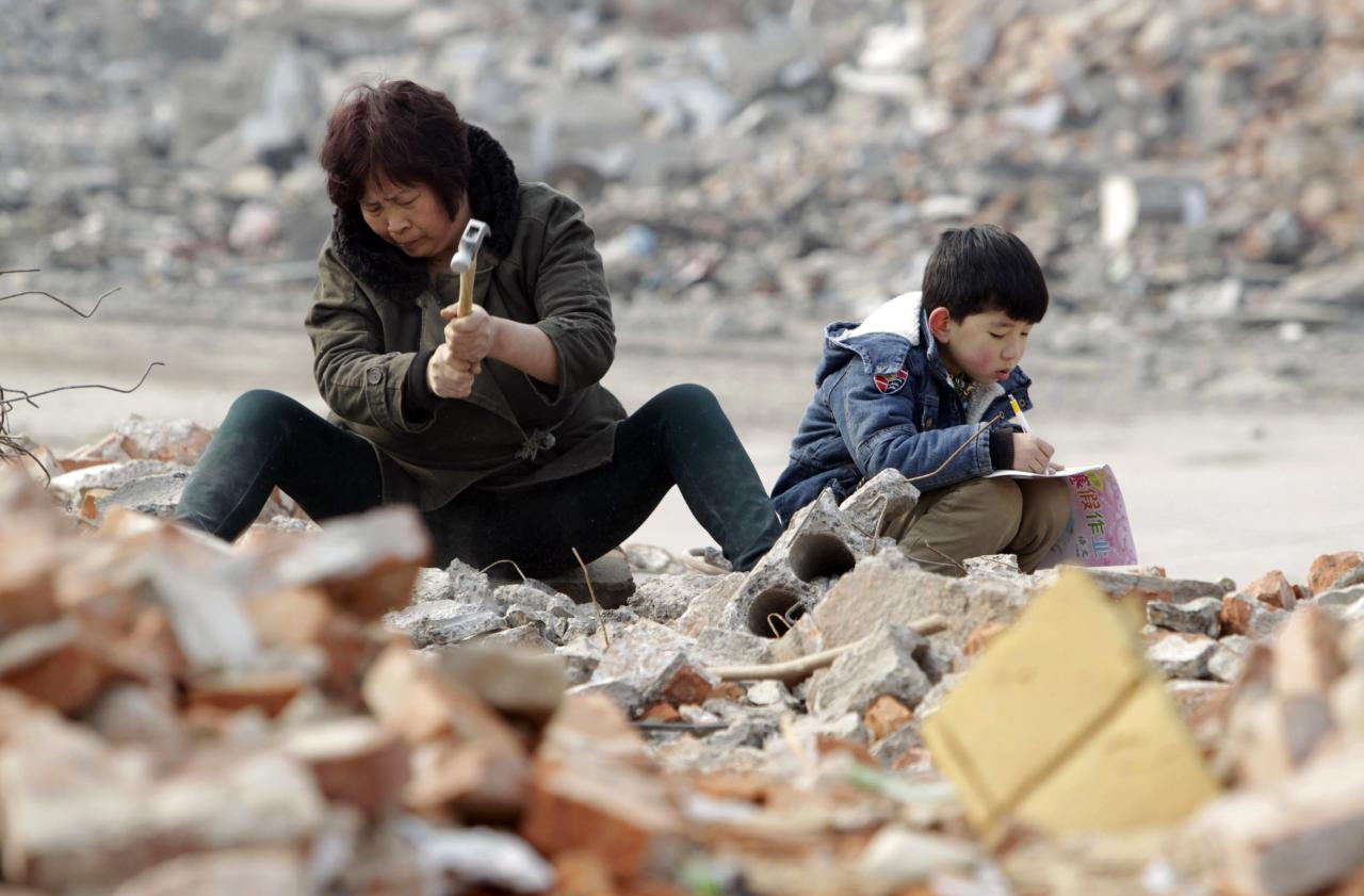 Primary school student Lele (R), 7, does his homework as his grandmother smashes concrete to look for recyclable steel bars at a demolition site in Zhengzhou, Henan province February 3, 2015. Lele's father was diagnosed with Leukemia four years ago and the family has been struggling to pay the medical bills. He came to help his grandmother collect recyclable materials to make extra money when his winter vacation started 10 days ago, local media reported. Picture taken February 3, 2015. REUTERS/Stringer (CHINA - Tags: SOCIETY BUSINESS CONSTRUCTION POVERTY TPX IMAGES OF THE DAY) CHINA OUT. NO COMMERCIAL OR EDITORIAL SALES IN CHINA