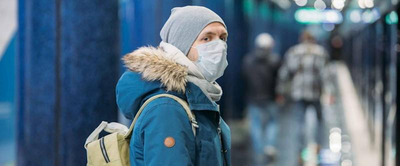 Ill young man feeling sick, wearing protective mask against transmissible infectious diseases and as protection against the flu in public and transportation.