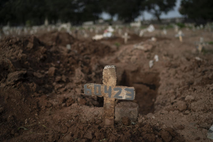 """A cross marks the grave of 57-year-old Paulo Jose da Silva, who died from the new coronavirus, in Rio de Janeiro, Brazil, Friday, June 5, 2020. According to Monique dos Santos, her stepfather mocked the existence of the virus, didn't use a mask, didn't take care of himself, and wanted to shake hands with everybody. """"He didn't believe in it and unfortunately he met this end. It's very sad, but that's the truth,"""" she said. (AP Photo/Leo Correa)"""