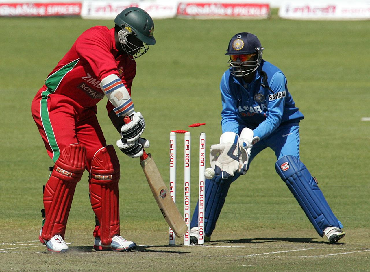 Zimbabwe batsman Brian Vitori looses his wicket as Indian wicket keeper Dinesh Kharthik looks on during the 4th match of the 5-match cricket ODI series between Zimbabwe and India at Queen's Sports Club in Harare on August 1, 2013. AFP PHOTO / Jekesai Njikizana        (Photo credit should read JEKESAI NJIKIZANA/AFP/Getty Images)