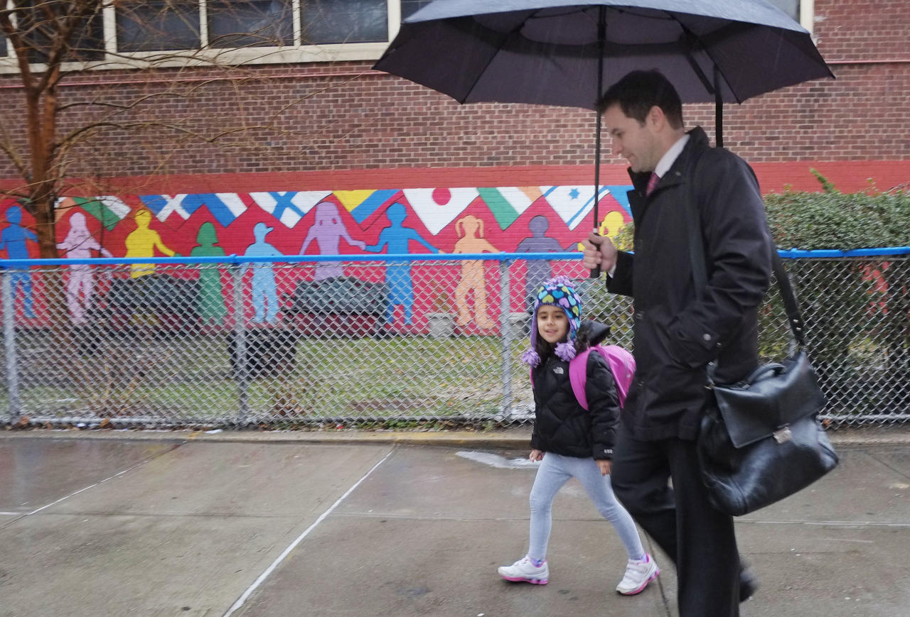 Matthew Mosca takes his daughter, Ella, to her kindergarten class at Public School 33, Wednesday, Jan. 16, 2013 in New York. Mosca said his 5-year-old usually takes the bus from their home on Manhattan's East Side, but took a taxi today. More than 8,000 New York City school bus drivers and aides went on strike over job protection Wednesday morning, leaving some 152,000 students trying to find other ways to get to school. (AP Photo/Mark Lennihan)
