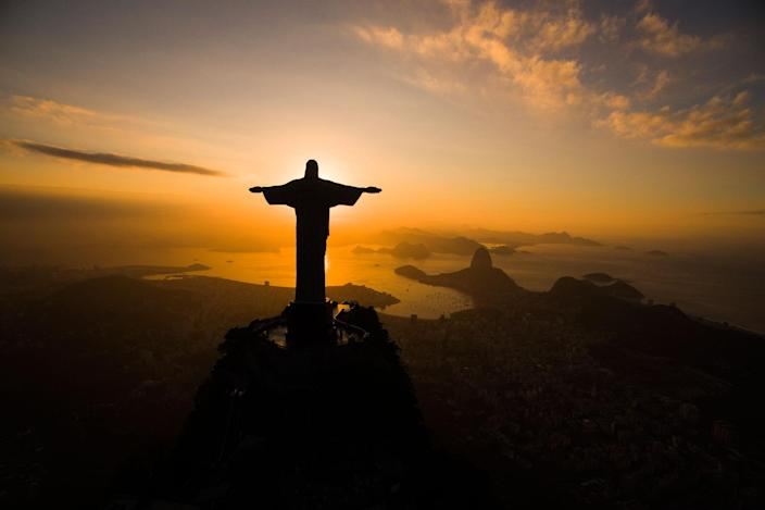 <p>JUL. 19, 2016 — The sun rises behind the Christ the Redeemer statue, above the Guanabara bay in Rio de Janeiro, Brazil ahead of the 2016 summer Olympics. (Felipe Dana/AP) </p>