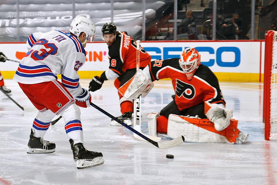 PHILADELPHIA, PA - MARCH 27: Adam Fox #23 of the New York Rangers attempts a scoring chance against Ivan Provorov #9 and Brian Elliott #37 of the Philadelphia Flyers at the Wells Fargo Center on March 27, 2021 in Philadelphia, Pennsylvania.  (Photo by Len Redkoles/NHLI via Getty Images)