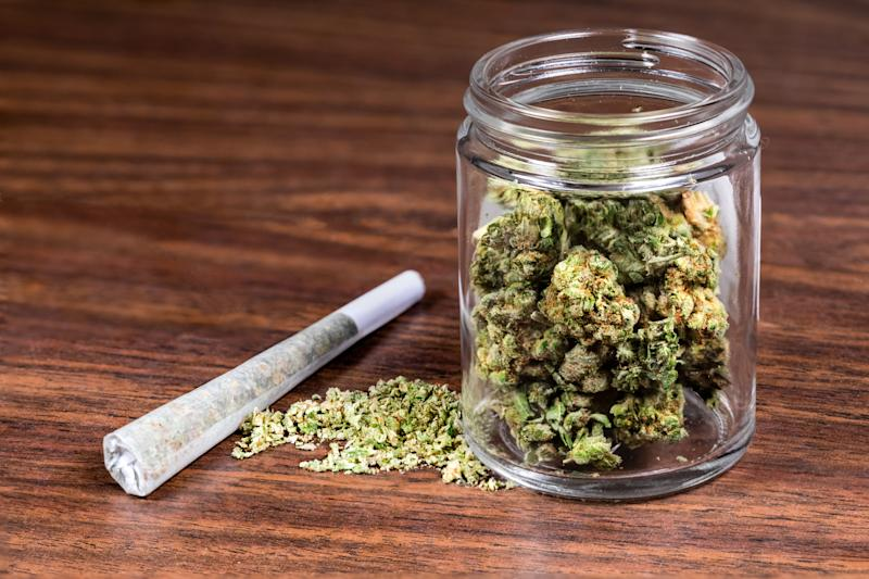 Glass jar of dried marijuana buds, with ground-up cannabis and a joint on a wooden table next to the jar.