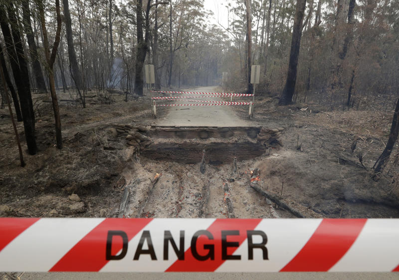 Timbers from a small bridge smolder after fire destroyed the crossing near Burrill Lake, Australia, Sunday, Jan. 5, 2020. Milder temperatures Sunday brought hope of a respite from wildfires that have ravaged three Australian states, destroying almost 2,000 homes. (AP Photo/Rick Rycroft)