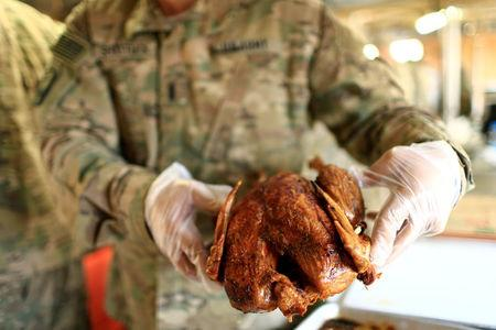 A U.S. soldier serves turkey to fellow soldiers to celebrate Thanksgiving Day inside the U.S. army base in Qayyara, south of Mosul, Iraq November 24, 2016. REUTERS/Thaier Al-Sudani