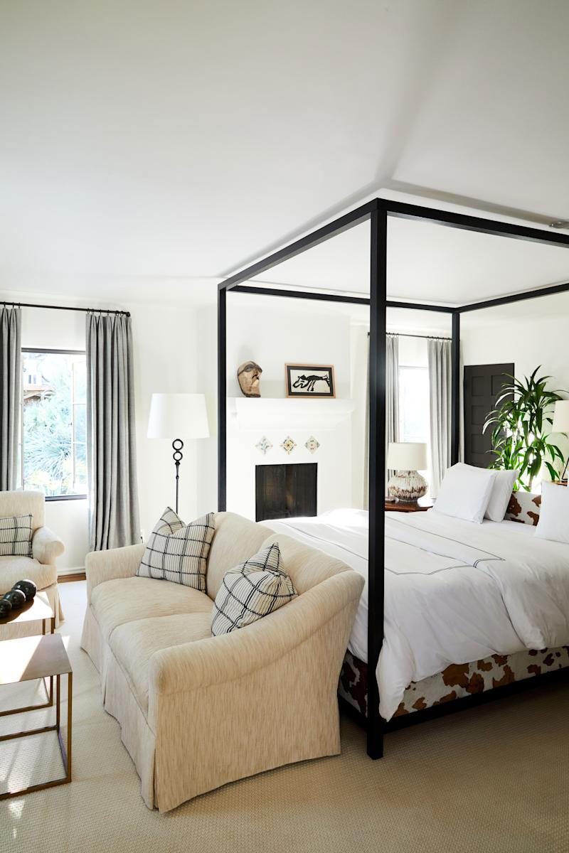 Romualdez designed the master suite's four-poster bed, which is partially covered in Cavallini hair-on hide. Above the mantel is an antique African mask and a painting by the late Dutch artist Karel Appel. Custom rolled-arm seats (with throw pillows upholstered in Zak and Fox's El Rais fabric) add warmth to the otherwise masculine space.