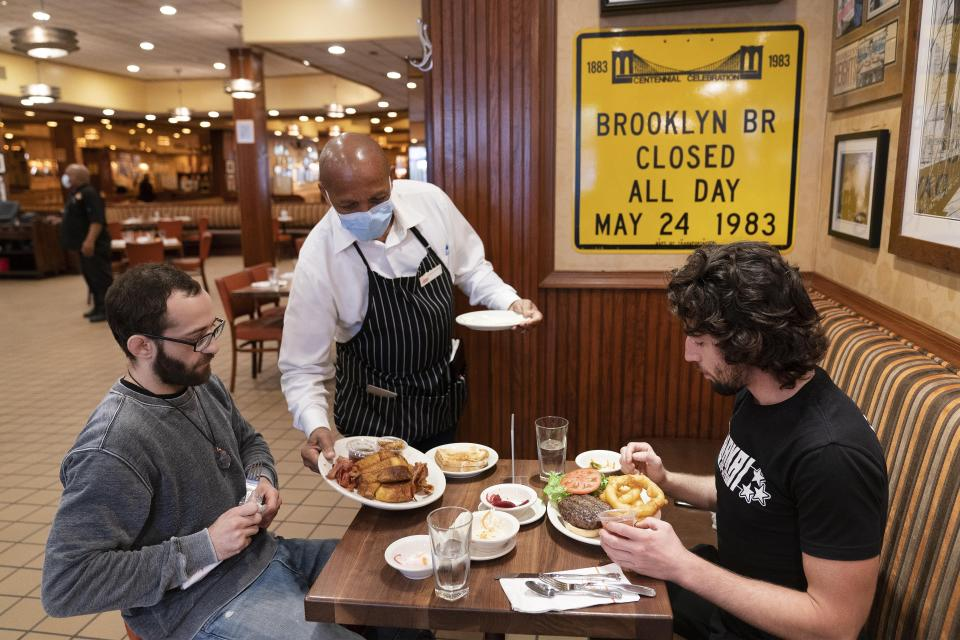 FILE - In this Sept. 30, 2020, file photo, Waiter Lenworth Thompson serves lunch to David Zennario, left, and Alex Ecklin at Junior's Restaurant in New York. New York City will soon require proof of COVID-19 vaccinations for anyone who wants to dine indoors at a restaurant, see a performance or go to the gym, Mayor Bill de Blasio announced Tuesday, Aug. 3, making it the first big city in the U.S. to impose such restrictions.(AP Photo/Mark Lennihan, File)