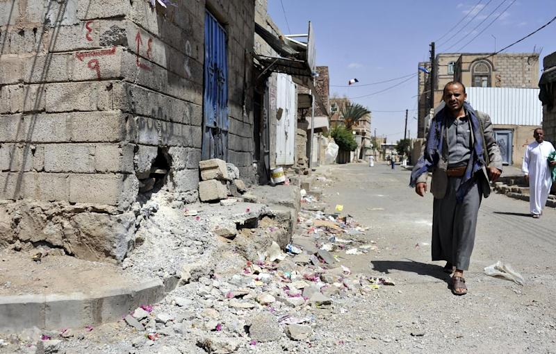 An armed Shiite rebel walks past a sidewalk damaged by a rocket attack, during clashes between rebels and government forces, in the capital Sanaa on September 19, 2014 (AFP Photo/)