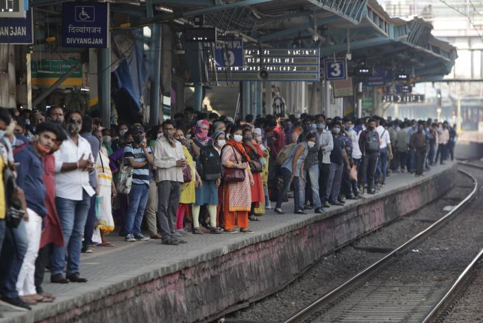 Commuters crowd the Dadar train station in Mumbai, India, Friday, Feb. 12, 2021. When the coronavirus pandemic took hold in India, there were fears it would sink the fragile health system of the world's second-most populous country. Infections climbed dramatically for months and at one point India looked like it might overtake the United States as the country with the highest case toll. But infections began to plummet in September, and experts aren't sure why. (AP Photo/Rajanish Kakade)