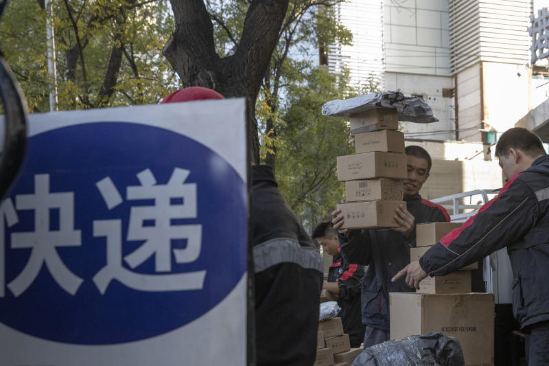 """Delivery men distribute parcels on the streets of Beijing on Monday, Nov. 11, 2019. Chinese e-commerce giants Alibaba and JD.com reported a total of more than $50 billion in sales on Monday in the first half of Singles Day, an annual marketing event that is the world's busiest online shopping day. The sign reads """"Delivery."""" (AP Photo/Ng Han Guan)"""