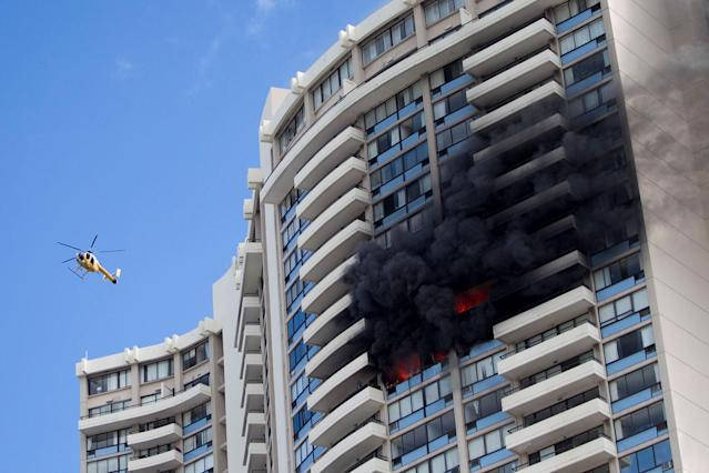 <p>A Honolulu Fire Department helicopter flies near a fire burning on a floor at the Marco Polo apartment complex, Friday, July 14, 2017, in Honolulu, Hawaii. (Photo: Marco Garcia/AP) </p>
