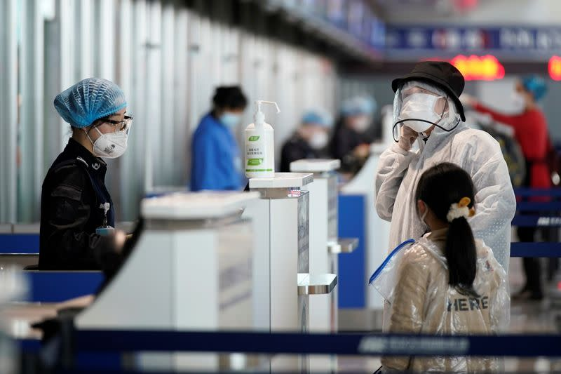 Travellers wearing protective gear are seen at a check-in counter at the Wuhan Tianhe International Airport