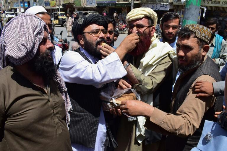 Supporters in Quetta, Pakistan of the hardline pro-Taliban party Jamiat Ulema-i-Islam-Nazaryati eat sweets as they celebrate the capture of cities in Afghanistan by the Taliban on August 13, 2021