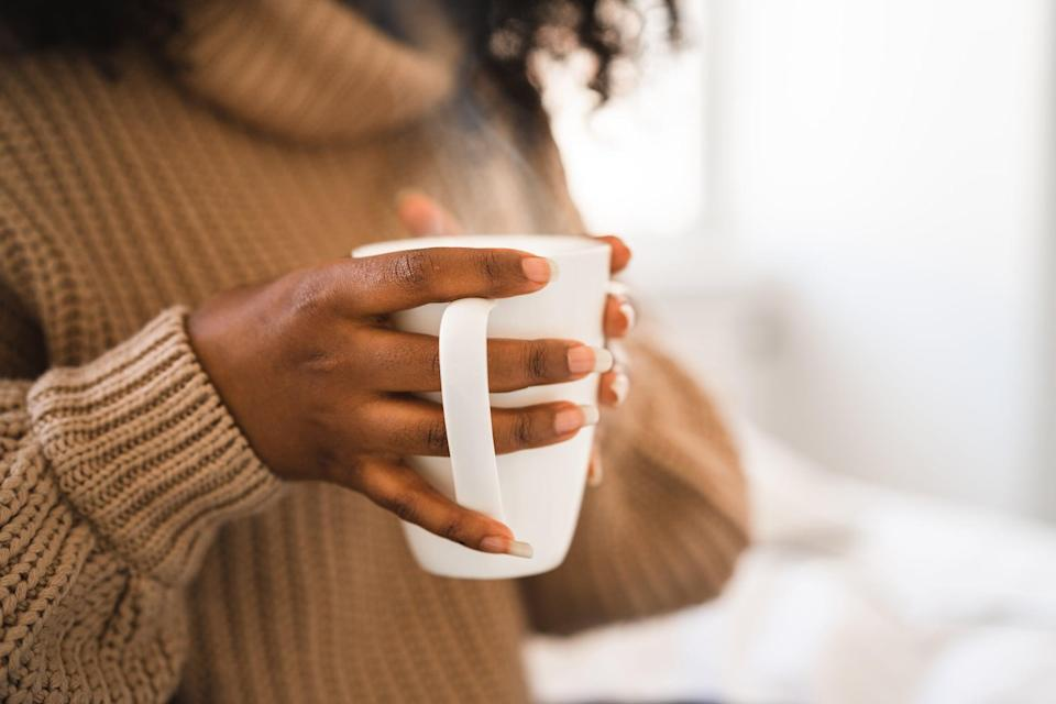A female university student is sitting in her bed, studying on her laptop. She is working from home for social distancing purposes. She is holding a cup of hot coffee and watching a web conference.